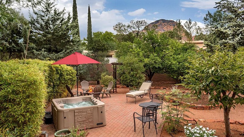 Private walled backyard with hot tub, and fire pit.