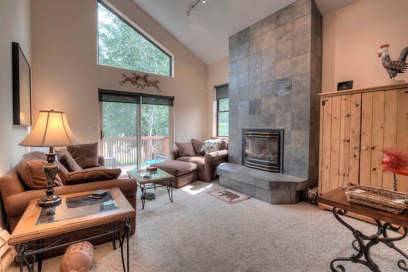 Impresionante sala de estar del piso principal con techos altos y una chimenea de pizarra actualizada