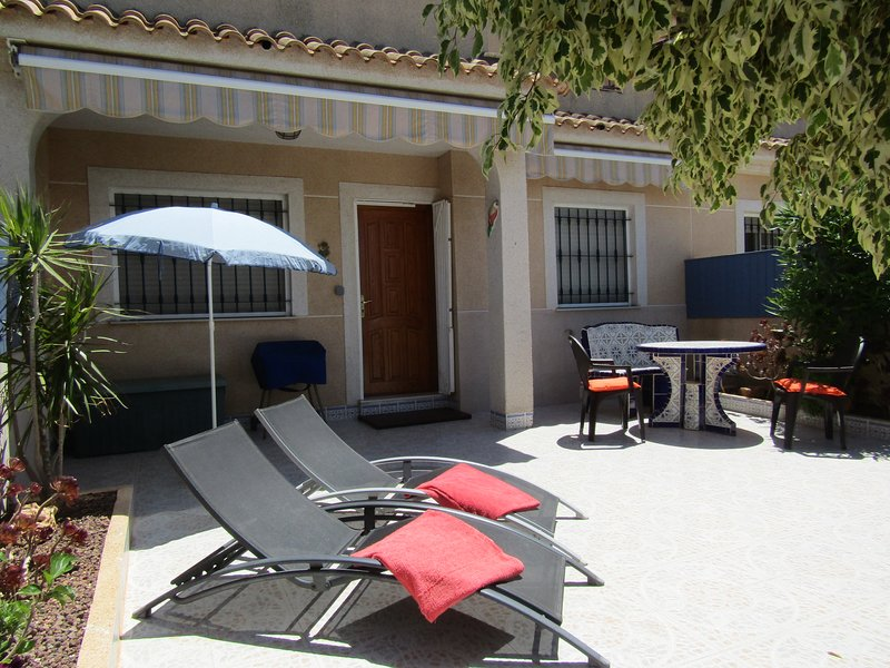 Pretty private terrace garden with BBQ, loungers and traditional Spanish tiled furniture.