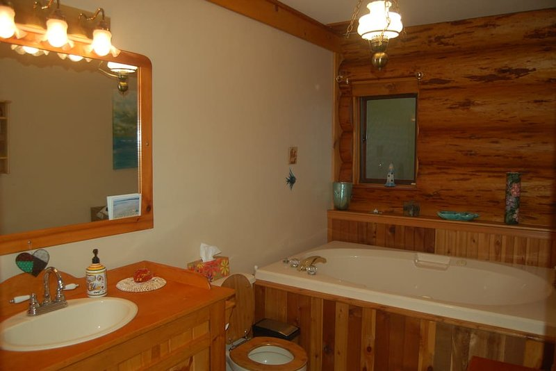 Main bathroom with large soaker tub next to master bedroom and den.