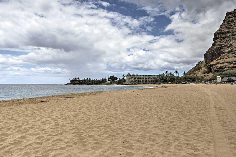 A costa de marfim-areia de 1 milha de distância em Makaha Beach.