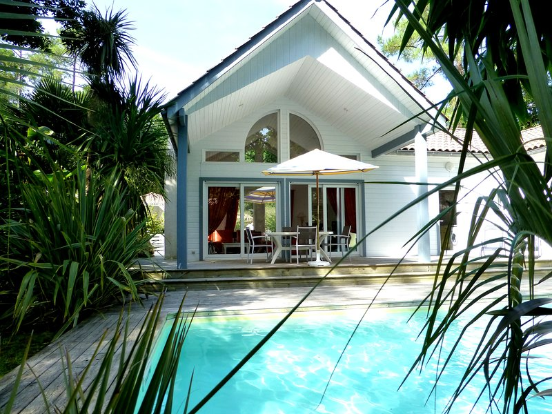 Pool view on covered terrace and barbecue fireplace