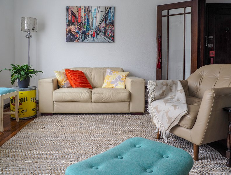 Living room complete with two seater leather couch and art of iconic Melbourne.