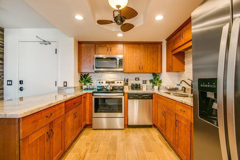 Electrodomésticos modernos de acero inoxidable y amplio espacio de trabajo en la encimera de granito.