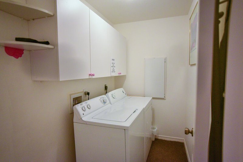 Laundry room with washer, dryer, iron, and ironing board
