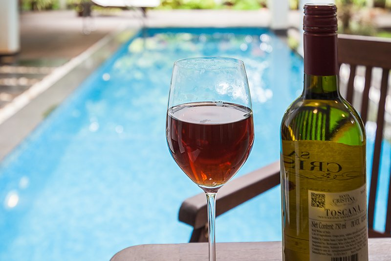 Wine in a glass beside the pool