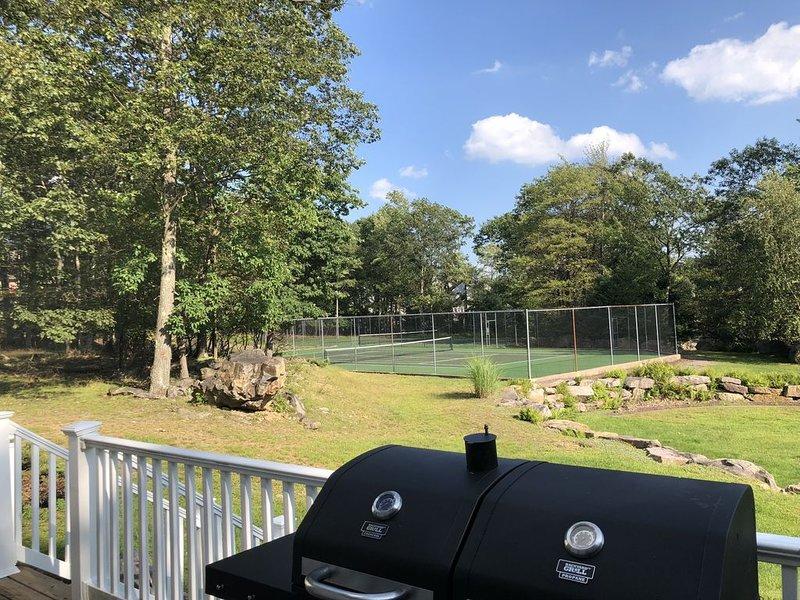 Vista do deck de quintal com quadra de tênis