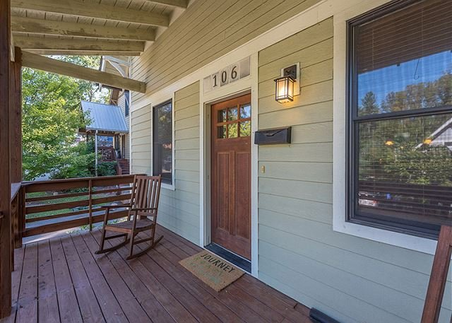 Covered front porch with rocking chairs.