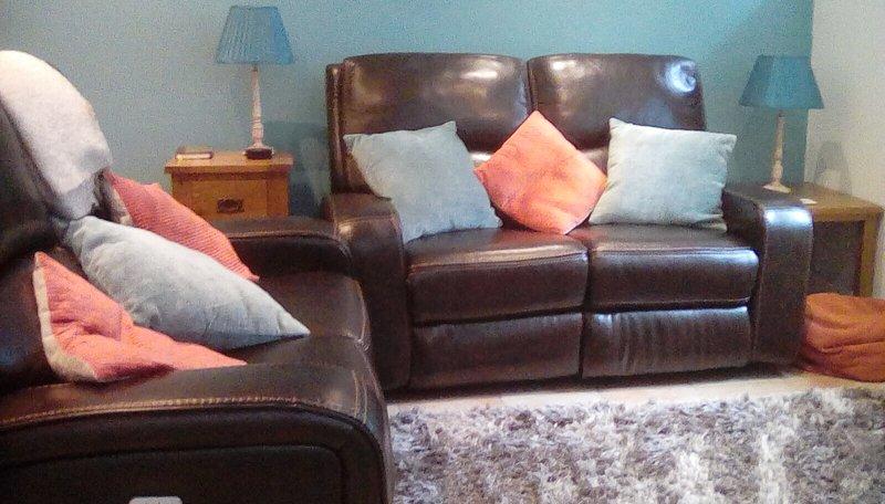 Cómoda área de descanso con sofás de cuero reclinables.