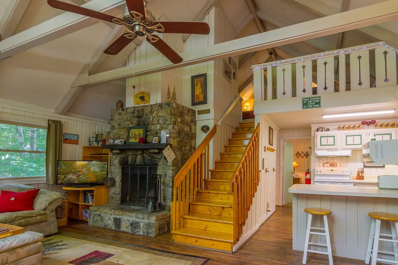 Benzine Farm Stone Fireplace, Flat Screen TV in Living Room; Stairs to Loft Viewed from Main Entry