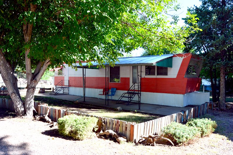 Exterior of vintage mobile home with patio and vintage seating.