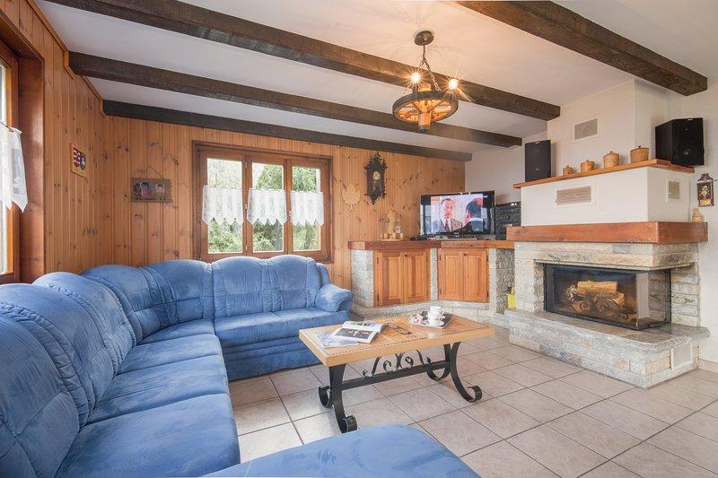 Salon ouvert avec meubles regroupés autour de la cheminée