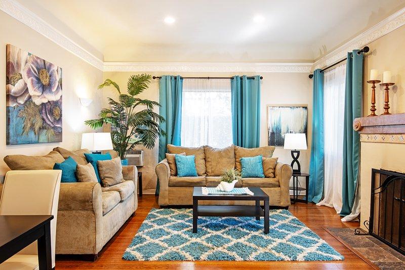 Sala de estar-sofá-cama, piso de madeira, tectos altos, unidade de parede a / c, lareira decorativa