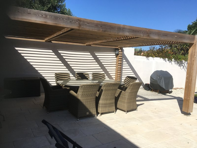 Courtyard with pergola, gas bbq and sun loungers.