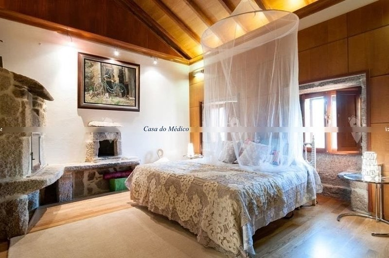 Room with Queen bed and traditional stone oven with fireplace. Complete bathroom.