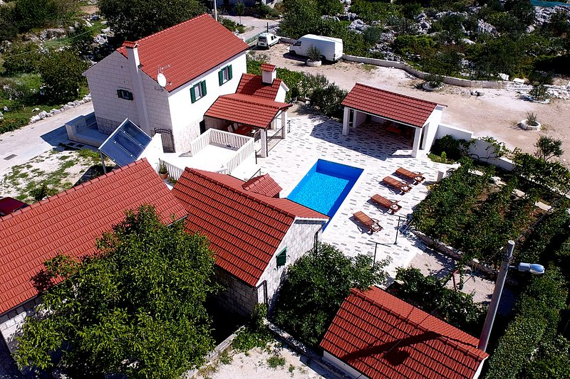 Daytime aerial view of the villa and all its structures forming its intimate and serene courtyard