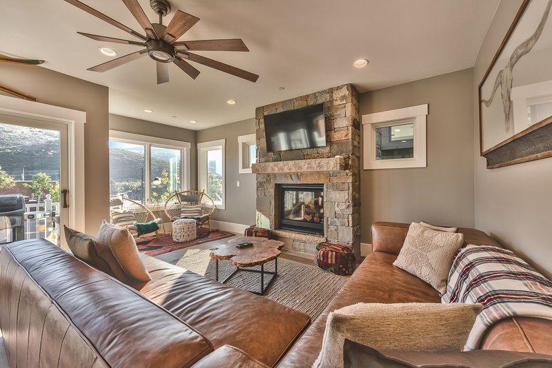 """Nivel 2: sala de estar decorada profesionalmente con un sofá seccional de cuero, Samsung Smart TV de 50 """"y chimenea a gas"""