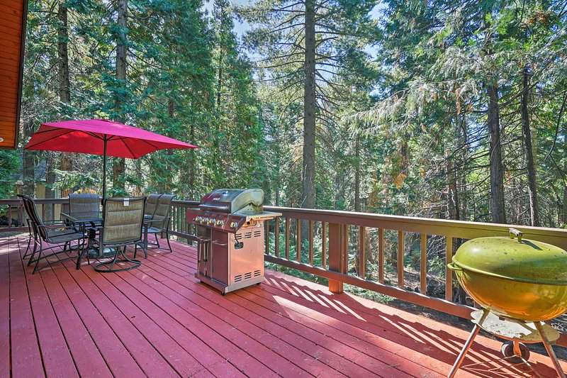 The secluded home boasts a wraparound deck with views of surrounding trees.