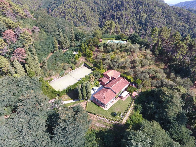 Overview of the villa with pool and tennis court