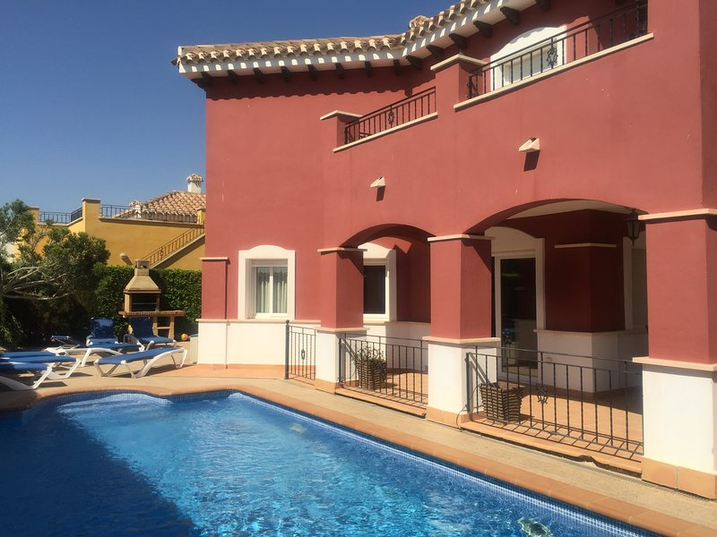 The heated pool and sun loungers at the rear of the villa.