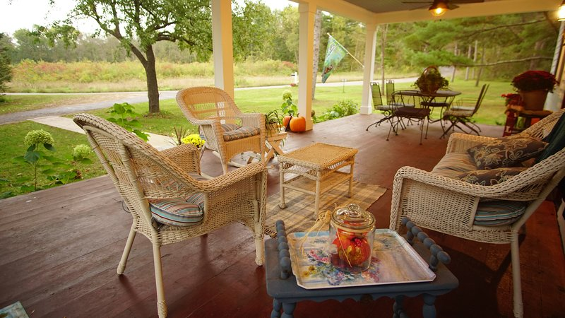 Front porch includes sitting area and dining area.