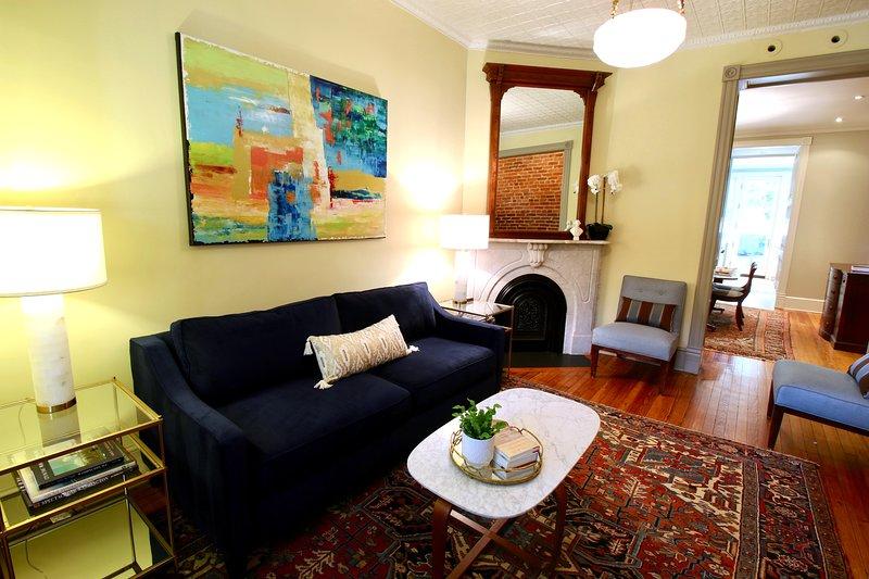 Salon avant avec cheminée en marbre et œuvres d'art originales à l'huile.