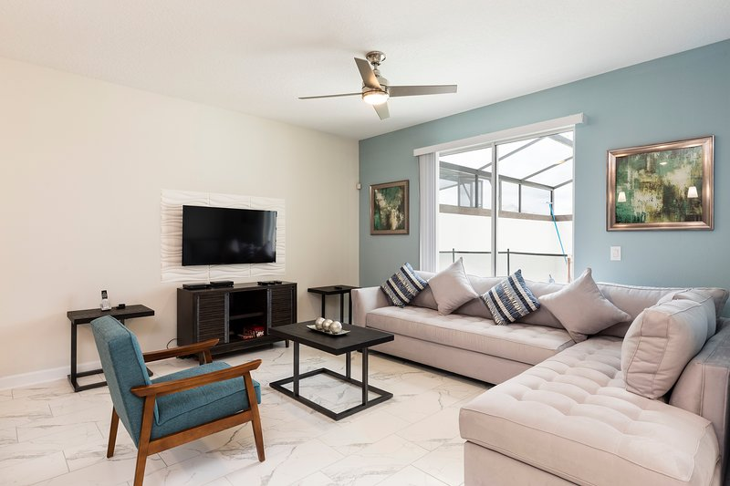Fully furnished living room with TV, sofa and table