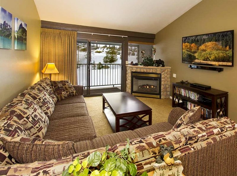 Cozy family room with balcony that overlooks mountains and trees, and lift.