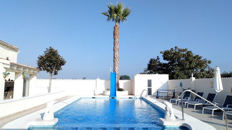 Vista da piscina com toboágua, duche exterior com WC e terraço.