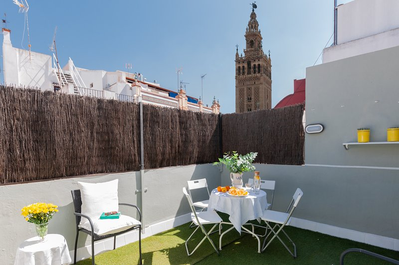 Terrace with views of the Giralda Tower. Table with chairs,deck chairs.