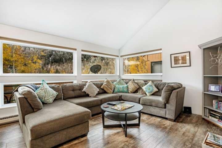 Cómoda sala de estar con ventanas luminosas que muestran impresionantes vistas de los bosques de álamos y pinos, bandas de acantilados y bosques.