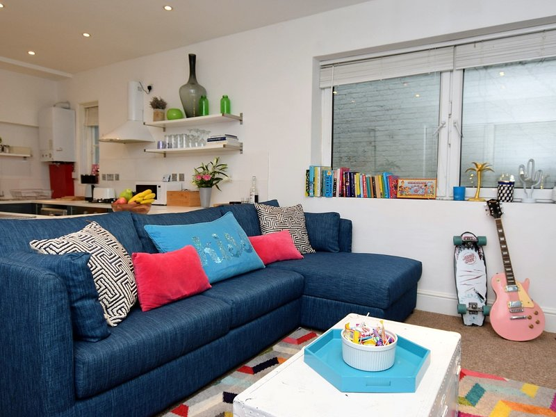 Snuggle into the open plan living area of this colourful coastal apartment