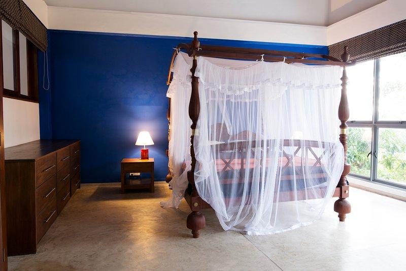 chambre immense avec fenêtre à l'avant et lit à baldaquin king size, ventilateur, bureau, armoire