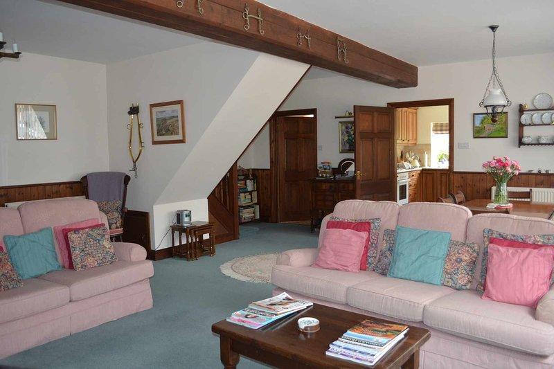 La sala de estar de planta abierta, con muchos asientos cómodos ...