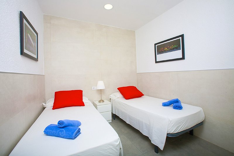 Room 2: It has two single beds, bedside table with lamp, wardrobe and balcony.