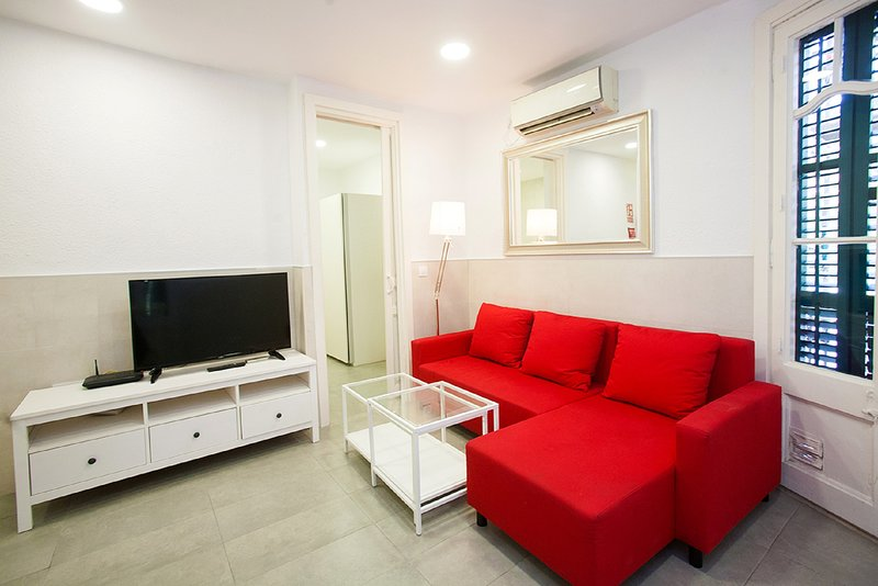 The living room has an armchair, TV, air conditioning, and a balcony.