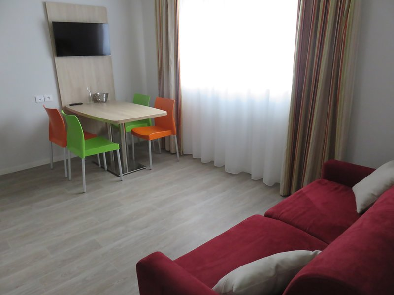 Relax in the bright living area with comfortable sofa and TV.