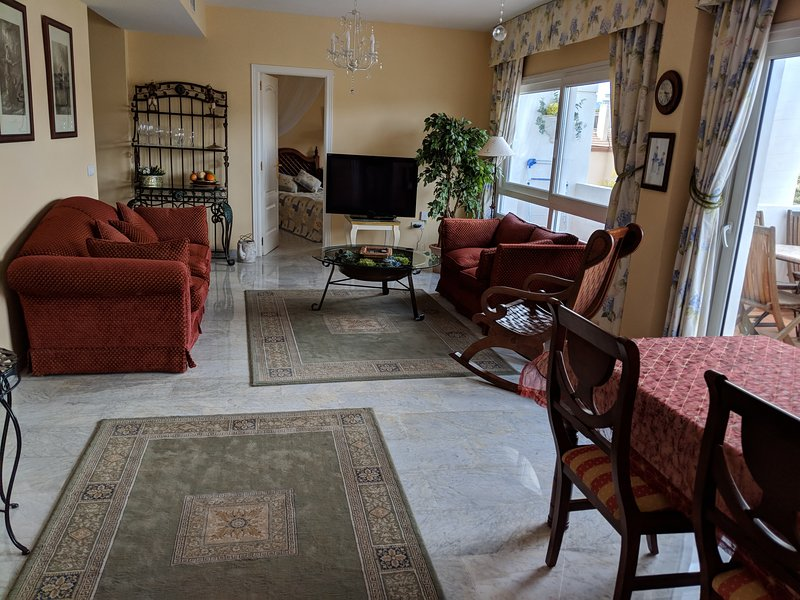 Amplia sala de estar con aire acondicionado, puertas a la terraza.