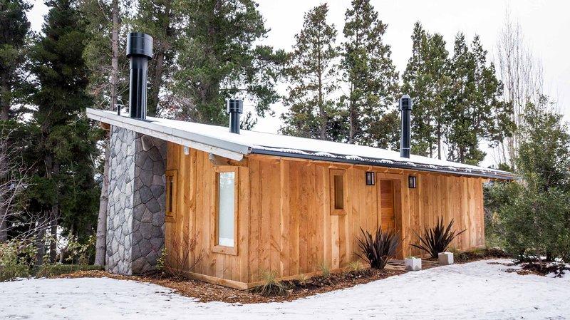 Entrada a la cabaña de madera y piedra