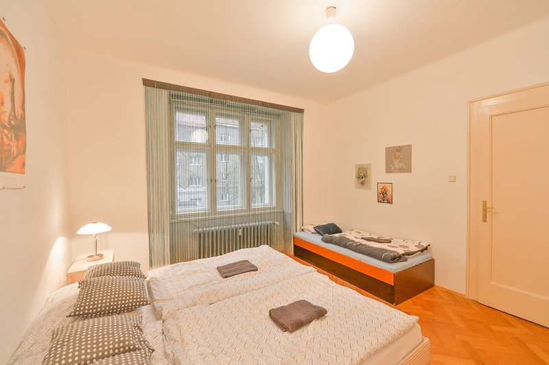 Bedroom with king size bed, single bed and courtyard view