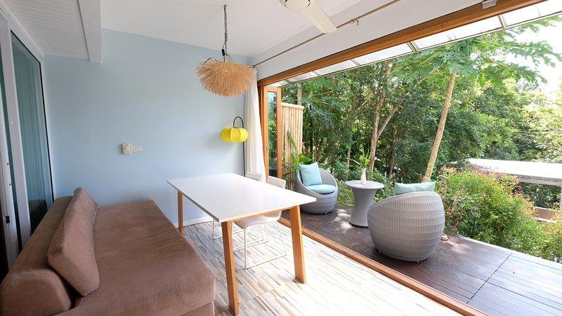 Table à manger et terrasse vue piscine et jardin.
