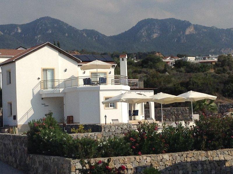 Villa Guzel Manzara (hermosa vista) con montañas en la parte trasera y el Mediterráneo en frente.