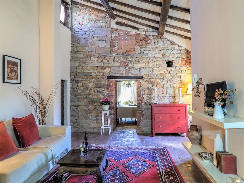The charming living room with exposed stone walls amd beamed ceilings