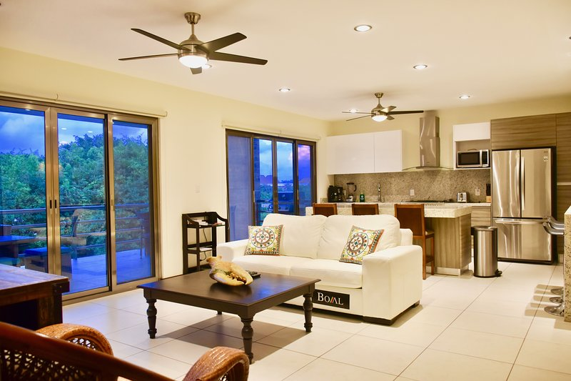 Living room with open plan kitchen and balcony access.