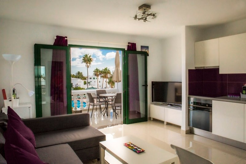 Beautiful Lounge with double doors opening onto spacious balcony with pool and sea views.