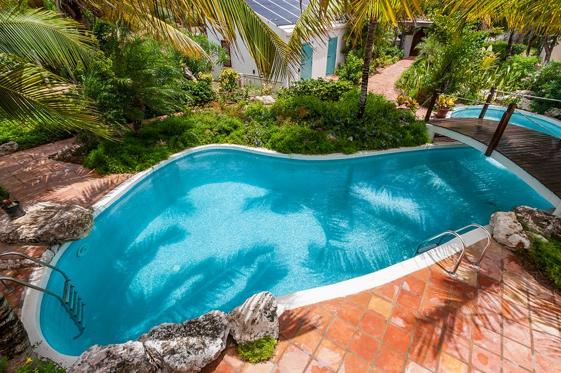 Schwimmen Sie in unserem Lagunenpool inmitten tropischer Gärten und schwimmen Sie unter unserer Eingangsbrücke