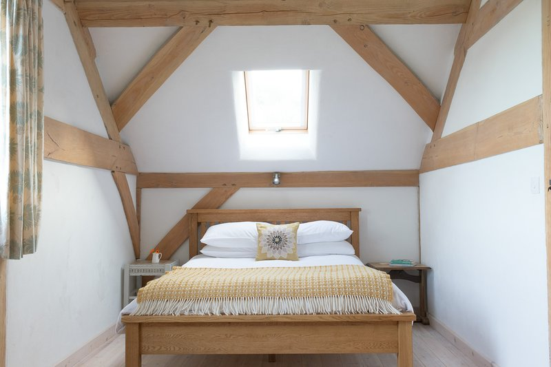 upstairs bedroom with king bed, single bed, TV, DVD and views across the kitchen garden