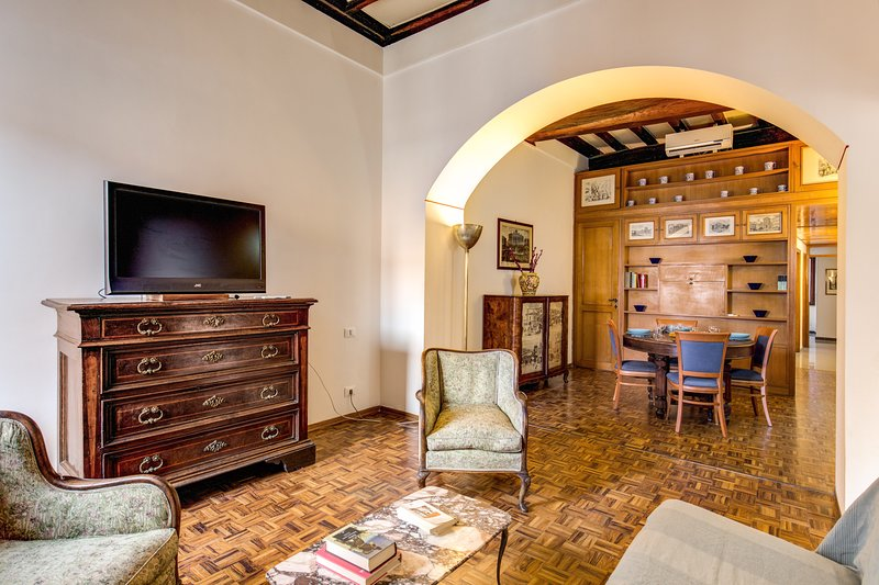 Living room with sofa, AC/heater, TV, dinner area and amazing view of the Trevi Fountain