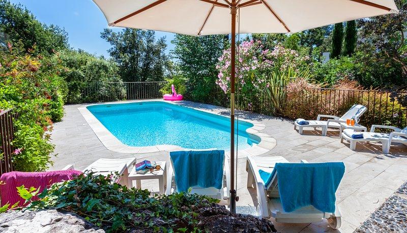 La piscina en Lou Messugo rodeado de flores.