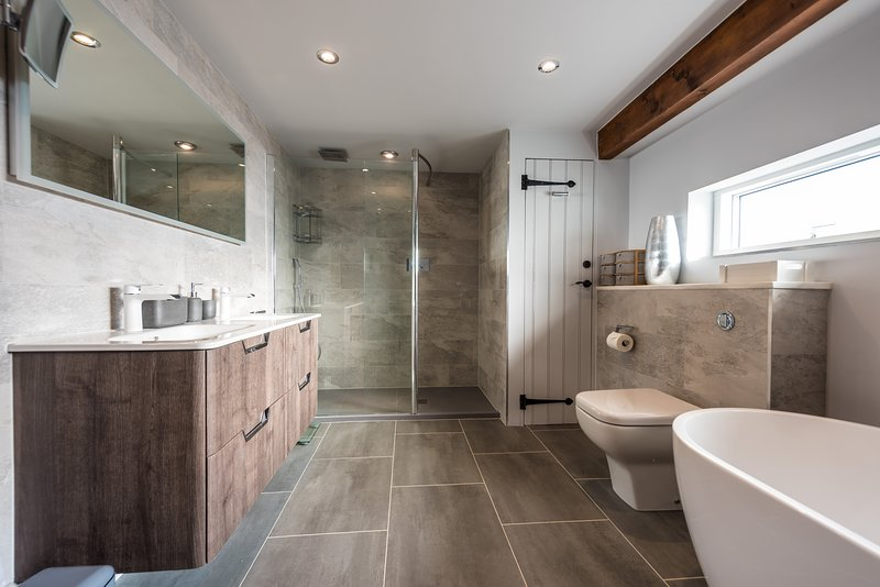 Family Bathroom with double-sink, walk-in shower and TV.
